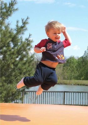 A joyful toddler catches some air on the jumping pillow at Great Country Farms.