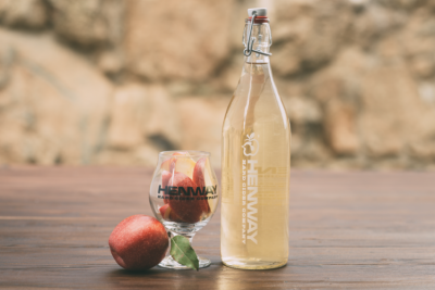 Henway Hard Cider growler displayed with a logo glass filled with Great Country Farms Apples