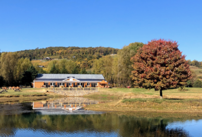 Henway Hard Cider's new building with the pond next to Great Country Farms in the foreground and the Blue Ridge Mountains in the background.