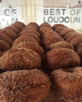 Cider Donuts stacked in the foreground with Great Country Farms Best of Loudoun Award Banner in the background