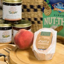 Zulla Cheese from Village Cheese works pictured in the Great Country Farms Market with fresh peaches and jams and jellies.