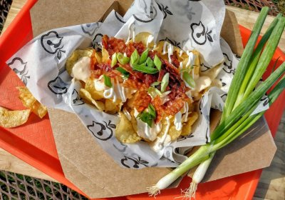 Box of Irish Nachos from the Henway Hard Cider kitchen filled with potato chips, sour cream, scallions and salsa