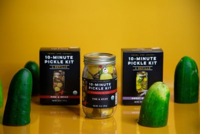 Pickling perfection cucumber on a fork with Johnny and Pearl pickling spice boxes