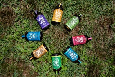All the flavors of Mad Magic Ginger Lemon Kombucha displayed on a circle in the grass in the farm Market at Great Country Farms