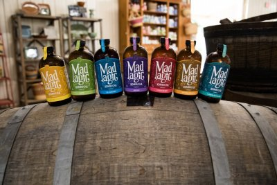 All the flavors of Mad Magic Ginger Lemon Kombucha displayed on the side of a wine barrel in in the farm Market at Great Country Farms