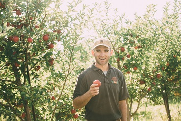 Great Country Farms Pick your own Apple Orchard Manager proudly holds up an apple in the apple orchard at Great Country Farms