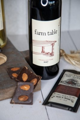 A bottle of Bluemont Vineyard's Farm Table Red Wine is displayed with Farmhouse Almond Chocolates in the Market at Great Country Farms