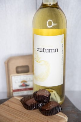 A bottle of Bluemont Vineyard's Farm Table Red Wine is displayed with Farmhouse Sea Salt Carmel Chocolates in the Market at Great Country Farms